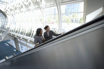 Two businesswomen ascending escalator, smiling, side view, elevated view