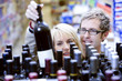 Couple shopping for wine in supermarket, choosing bottle from shelf, smiling