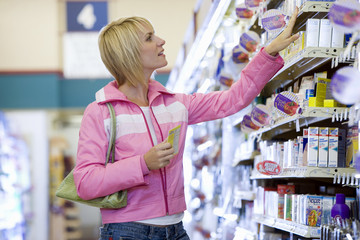 Woman shopping in supermarket, choosing item from shelf, side view