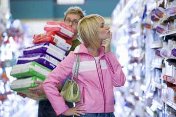 Couple shopping in supermarket, man struggling with stack of items, woman thinking