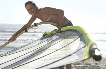 Young woman in bikini assembling windsurfer on sandy beach, smiling, side view, portrait