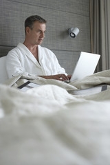 Businessman in bathrobe sitting in hotel bed, using laptop, surface level