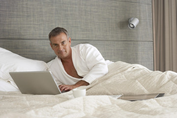 Businessman in bathrobe sitting in hotel bed, using laptop, smiling, portrait