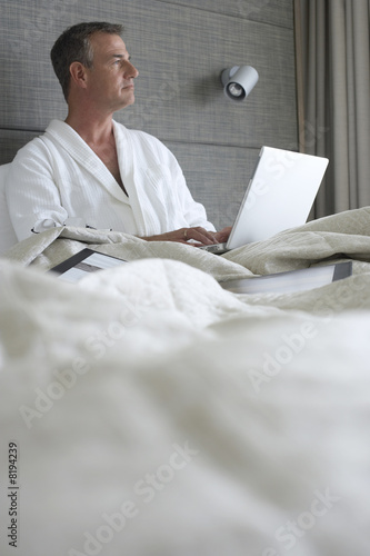 Businessman in bathrobe sitting in hotel bed, using laptop, thinking, surface level