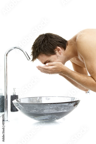Young man splashing his face with water