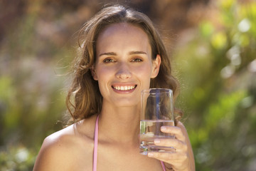 Young woman holding a glass of water, close-up
