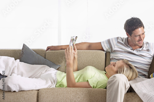 Couple relaxing on sofa at home, woman with head in man's lap, reading magazine, man with newspaper