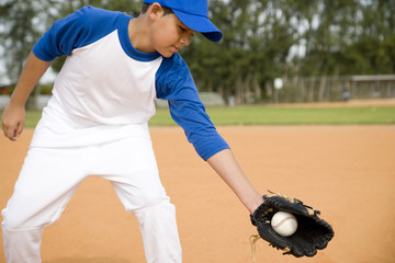 Boy catching baseball in glove