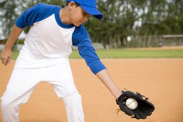 Boy catching baseball in glove