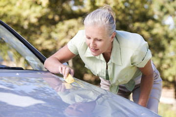 A senior woman cleaning her car