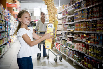 Naughty young girl emptying cereal packet in a supermarket