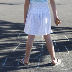 Young girl playing hopscotch, close-up