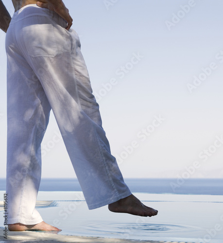 A man standing by a pool