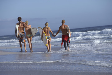 Two young couples walking in surf at beach, carrying surfboards, holding hands, smiling