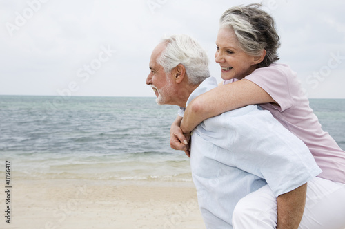 Senior man giving a senior woman a piggyback at the beach