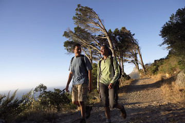 South Africa, couple hiking along mountain path, sea in background