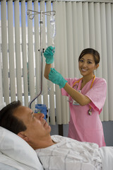 Nurse checking IV drip, smiling, male patient lying in hospital bed, side view