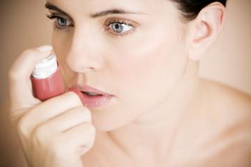 Female asthma sufferer using an inhaler