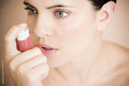 Female asthma sufferer using an inhaler