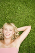 Beauty portrait of a woman laying in the grass in a tropical setting.