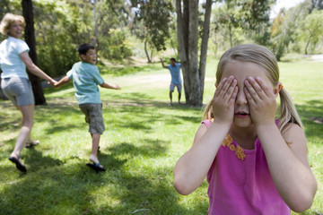 Family playing hide and seek in park, focus on girl (8-10) covering eyes in foreground