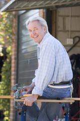Man at shed sitting on tool bench smiling
