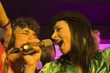 Close-up of a young couple singing in a nightclub