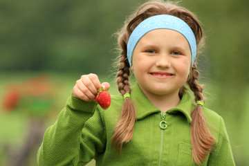 Little girl with a strawberry