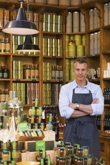 Male grocery shop owner in apron standing beside olive oil display, arms folded, smiling, portrait