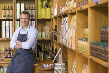Male grocery shop owner in apron standing beside shelf display, arms folded, smiling, portrait