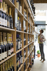 Female customer shopping in off-licence, looking at bottles of wine on shelf, tip-toeing, profile