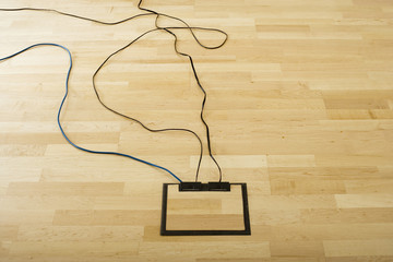 Cables connected to wooden floor socket in office