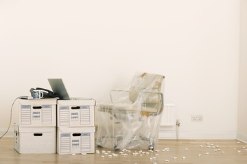 Office chair wrapped in plastic sheet beside laptop on stack of file boxes in empty office