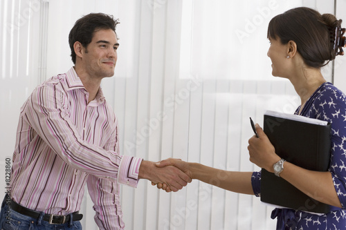 Businesswoman and businessman shaking hands in office, woman holding folder, smiling, side view