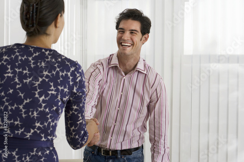 Businesswoman and businessman shaking hands in office, smiling