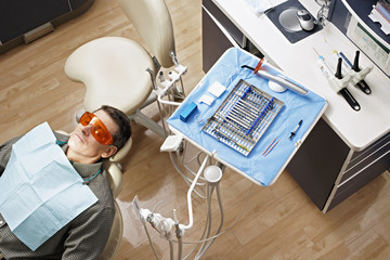 Male patient lying in dentist's chair beside tray of dental tools in dental surgery, overhead view