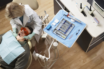 Female dentist examining male patient sitting in dentist's chair in dental surgery, overhead view