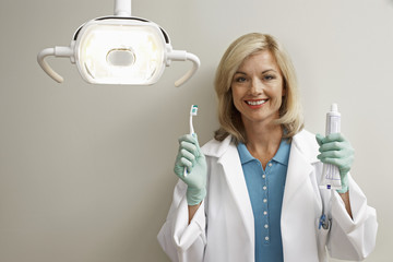 Female dentist holding toothbrush and toothpaste in dental surgery, smiling, front view, portrait