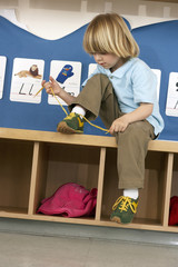Blonde boy (4-6) sitting on bench in classroom, tying shoelace, alphabet cards on wall (tilt)