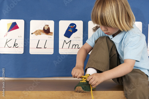 Blonde boy (4-6) sitting on bench in classroom, tying shoelace, alphabet cards on wall