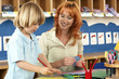 Boy (4-6) making card at desk in classroom, teacher assisting, smiling