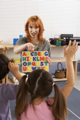 Children (4-6) learning the alphabet in classroom, hands raised, focus on teacher in background