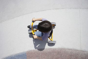 Boy (4-6) riding toy tricycle in playground, overhead view