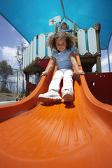 Girl (4-6) sliding down orange slide in playground, front view, surface level