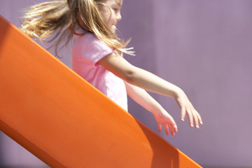 Girl (4-6) sliding down orange slide in playground, profile, mid-section