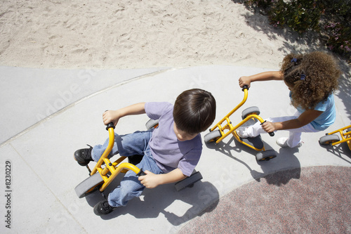 Boy and girl (4-6) riding toy tricycle and push scooter in playground, overhead view (tilt)