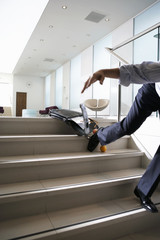 Businessman falling down steps in office lobby, low section