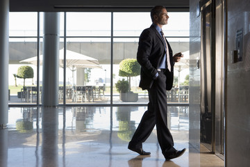 Businessman entering lobby elevator, profile