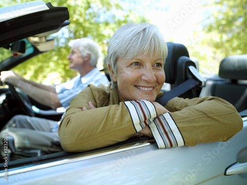 Senior couple driving in convertible car, woman leaning on door, smiling, side view (tilt)