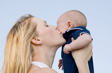 Mother Holding Son Up Kissing Him on Cheek